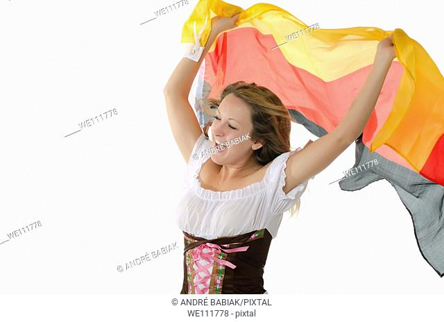 Young woman in dirndl dress cheering with Germany flag