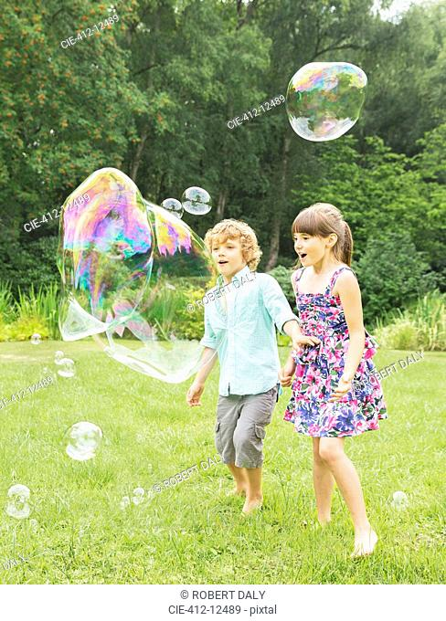 Children playing with bubbles in backyard