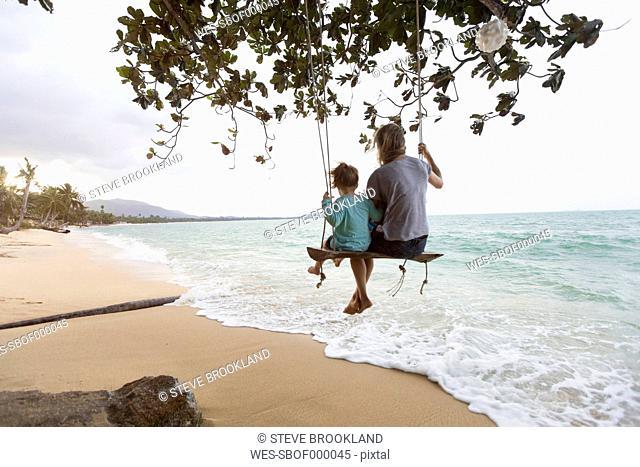 Thailand, family on beach, sitting on swing