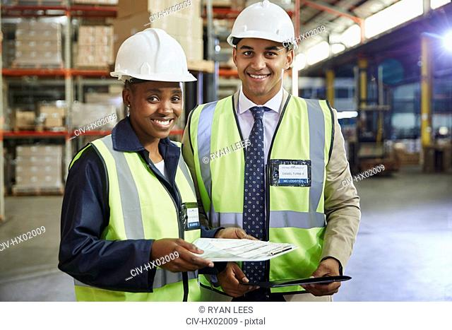 Portrait smiling manager and worker with paperwork in distribution warehouse