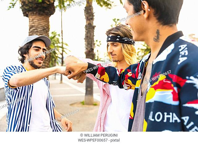 Multicultural group of three friends bumping fists