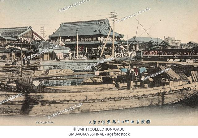Postcard picture of a Japanese Fishing Village showing a few boats docked on a wharf with several Japanese buildings in the background, Yokohama, Japan, 1904