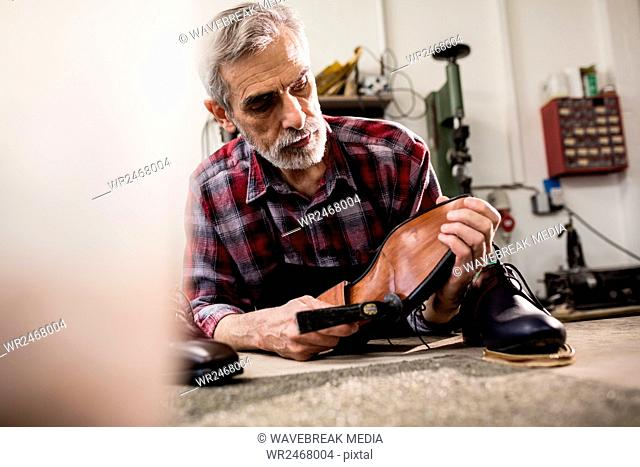 Cobbler hammering on the sole of a shoe