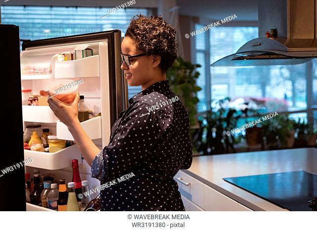 Happy young pregnant woman standing near refrigerator looking for food in the kitchen