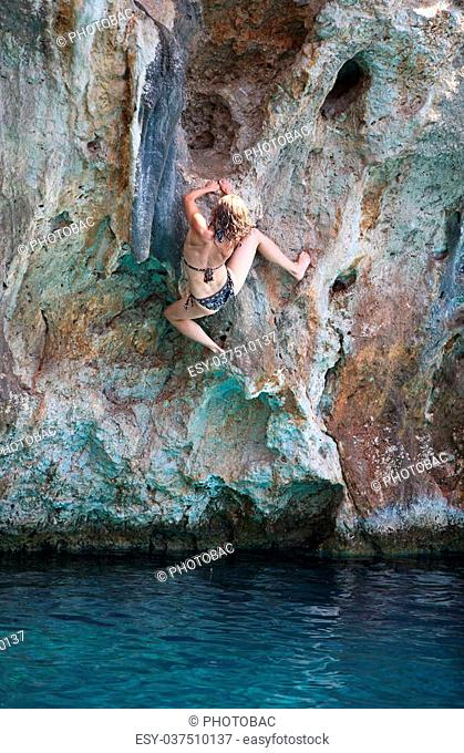 Deep water soloing, young female rock climber on face of cliff