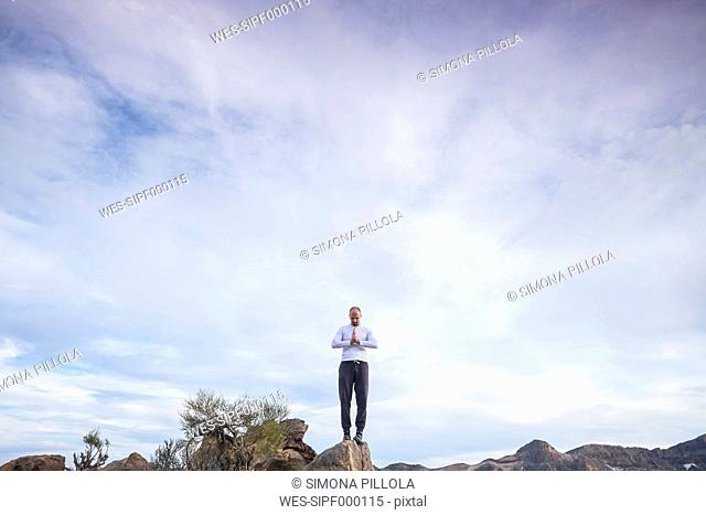 Spain, Tenerife, man in prayer position standing on a rock