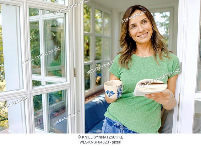 Smiling mature woman at home with book and coffee mug