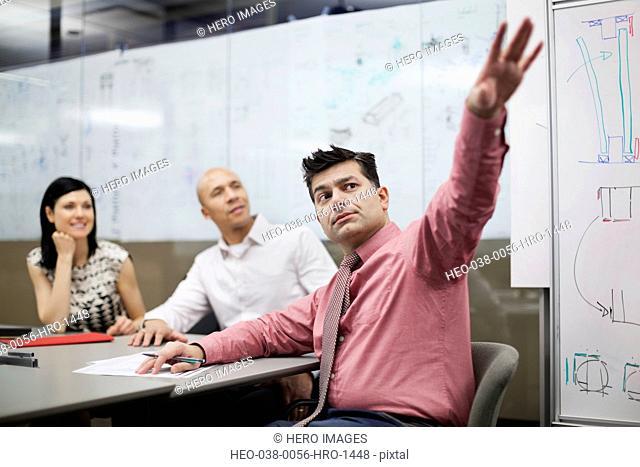 Mature businessman gesturing to white board presentation