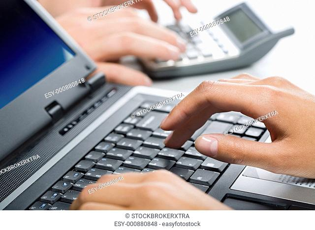 Hands typing a text on a laptop in a working environment