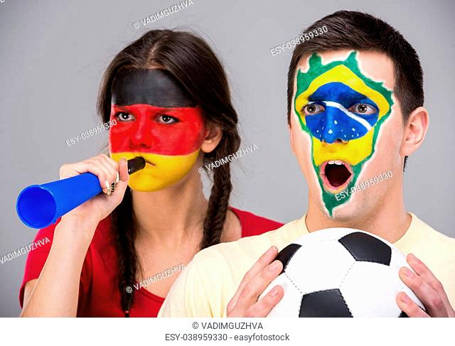 Two young fans with the flags of their countries painted on faces are holding a soccer ball. Germany and Brazil