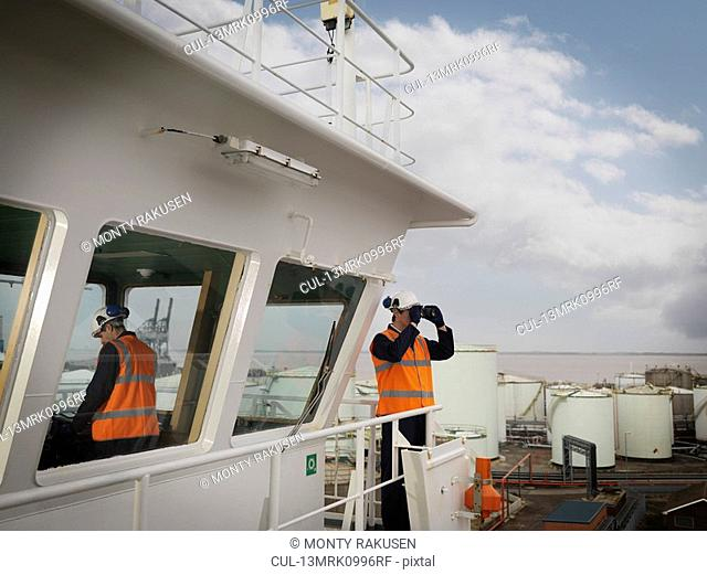 Port Worker With Binoculars On Ship