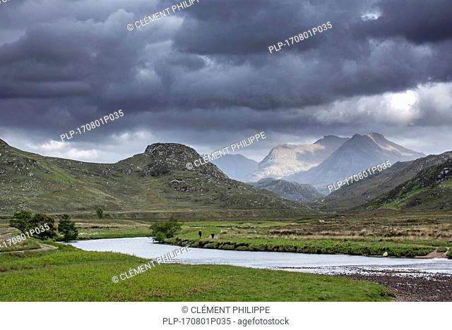 Two walkers walking on path along river and rain clouds forming in Wester Ross, Scottish Highlands, Scotland, UK