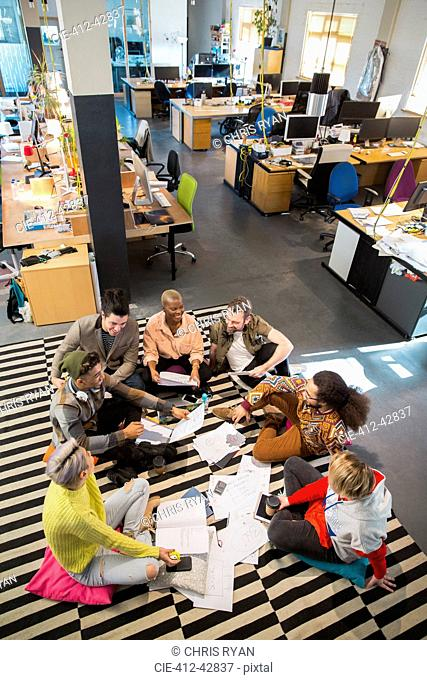 Creative business team meeting, brainstorming in circle on office floor