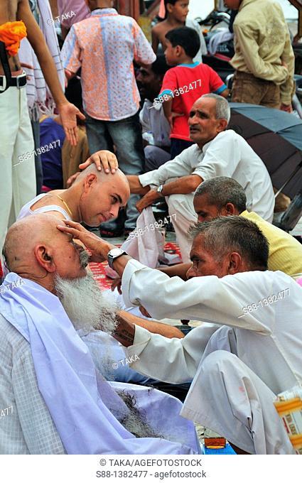 Pilgrims shaving hair for devotion to the God at Har Ki Pairi ghat by the Ganges River