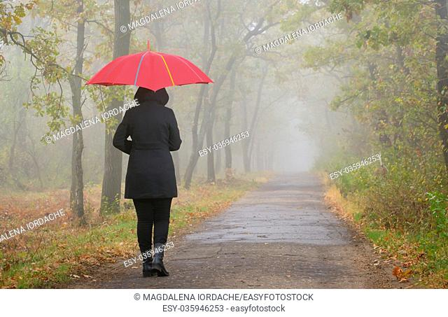 Depressed woman with red umbrella and foggy forest