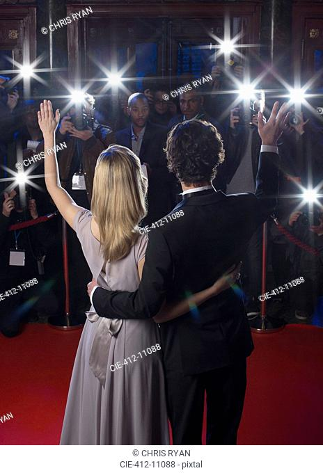 Rear view of well dressed celebrity couple waving to paparazzi on red carpet