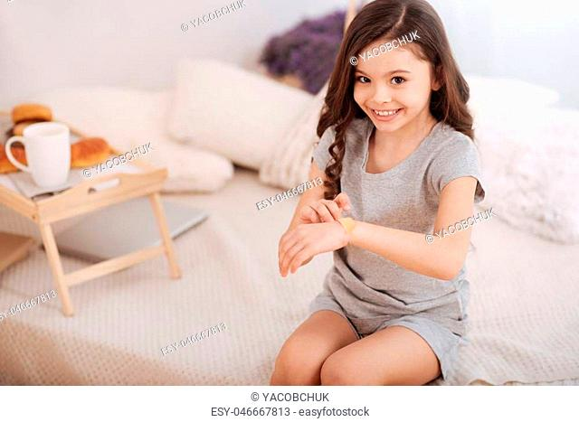 Full of positive emotions. Delightful attractive little girl sitting in the white colored room and putting adhesive bandage on her wrist while smiling