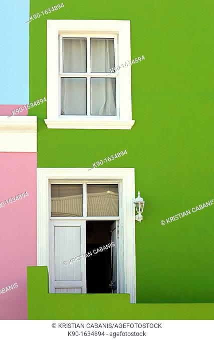 Green wall with one window and entrance door with white frame, clear, blue sky, Bo-Kaap Malay Muslim District, Cape Town, South Africa