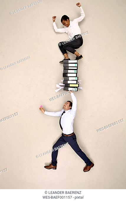 Businessman holding folders with female colleague on top