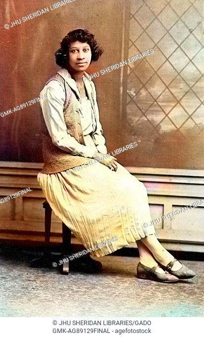 Full length sitting portrait, young African American woman, wearing light dress and vest, sitting on stool in front of backdrop, neutral expression, 1920