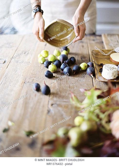 A woman at a domestic kitchen table. Arranging fresh fruit, black and green figs on a cheese board. Organic food. From farm to plate