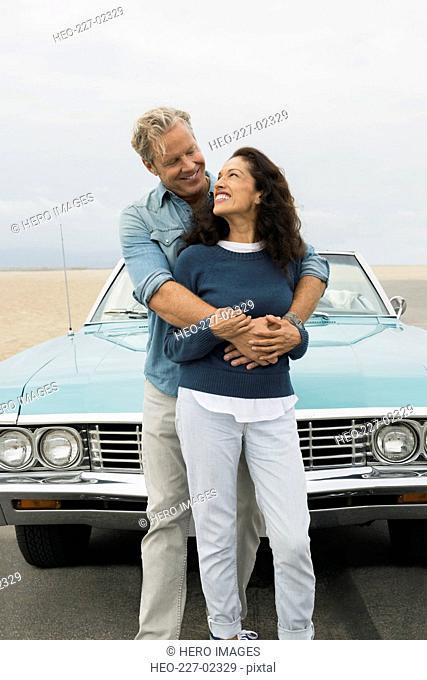 Smiling couple hugging at convertible at beach