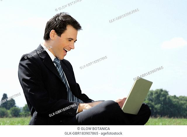 Businessman using a laptop and laughing