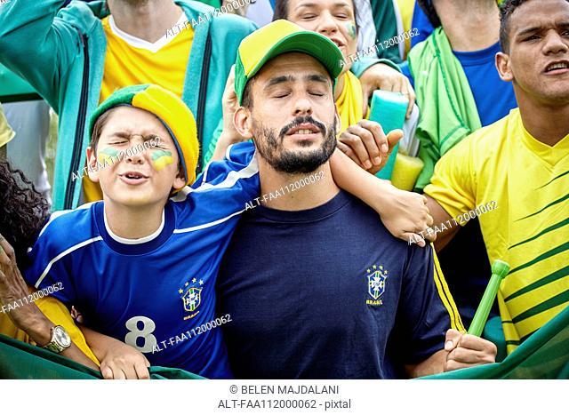 Brazilian football fans looking upset at football match