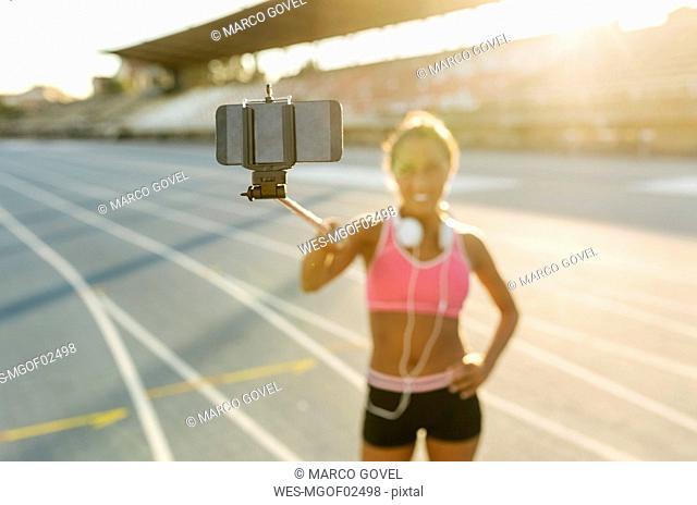 Female athlete taking selfies in stadium, holding selfie stick
