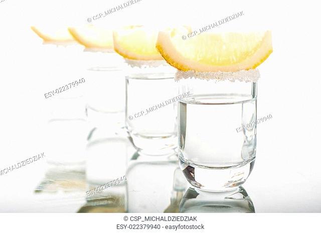 Four shots of vodka with lemon