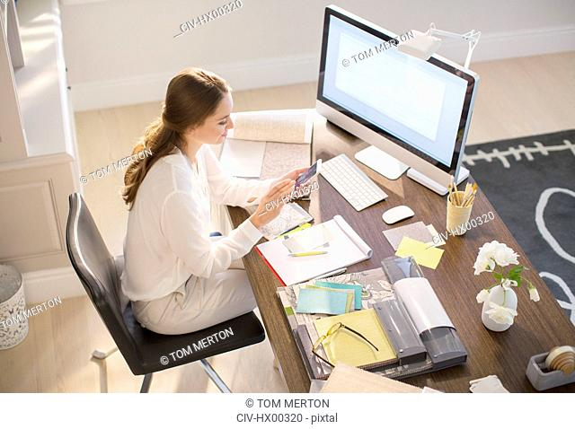 Interior designer texting on cell phone at desk in home office