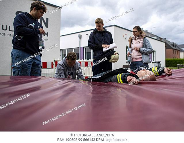 08 June 2019, North Rhine-Westphalia, Mönchengladbach: A firefighter lies exhausted, surrounded by his friends, on a mat after his assignment in competition