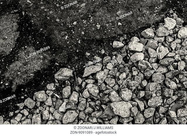 Rough gravel meets smooth Tarmac in black and white - using diagonal composition to highlight the different shapes and styles of rock present in this Abstract...