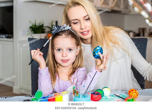 Mother And Daughter Painting Easter Eggs In Home. Girl with her mother learning to paint Easter eggs. Cozy home atmosphere. Easter