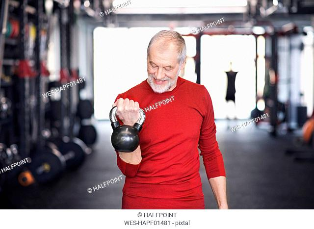 Senior man exercising with kettlebell in gym