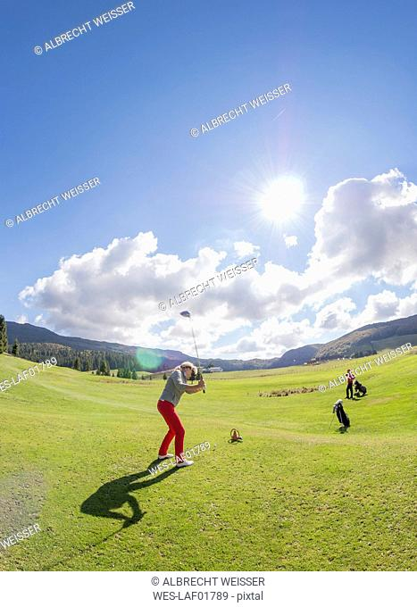 Italy, Veneto, Dolomites, senior couple on golf course