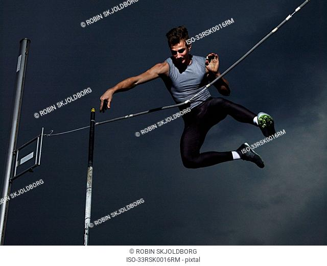 Man jumping midair in pole vault