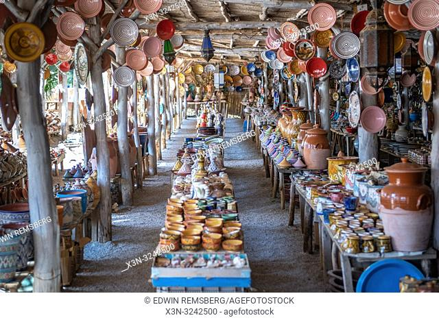 Outdoor marketplace with several tables full of pottery for sale, Tangier,Morocco