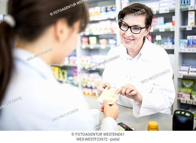 Pharmacist handing over medicine to customer in pharmacy