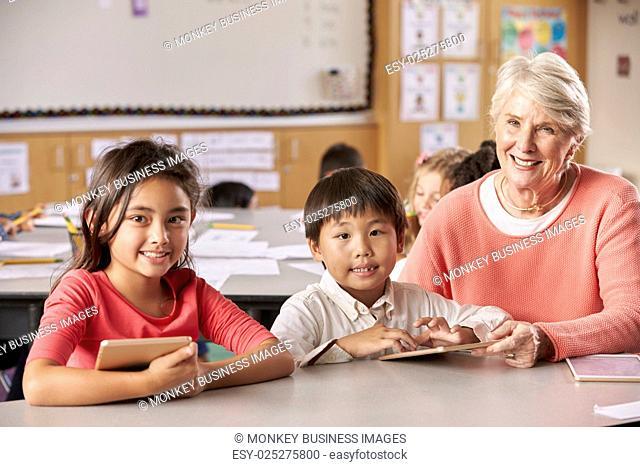 Senior teacher and elementary school pupils in classroom