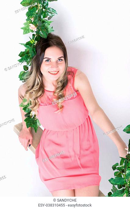 Beautiful young leggy blonde in a little pink dress and red high-heeled shoes on a swing, wooden swing suspended from a rope hemp, rope wrapped vine and ivy