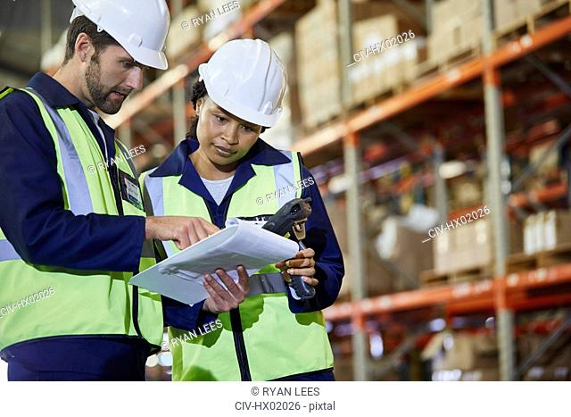 Workers with scanner and clipboard talking in distribution warehouse