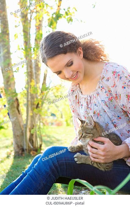 Teenage girl relaxing in garden petting cat
