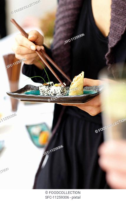 A woman eating sushi in a restaurant
