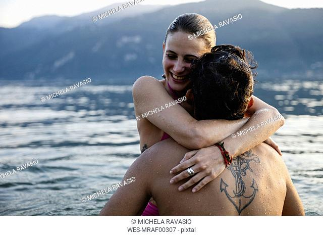 Happy young couple hugging in a lake