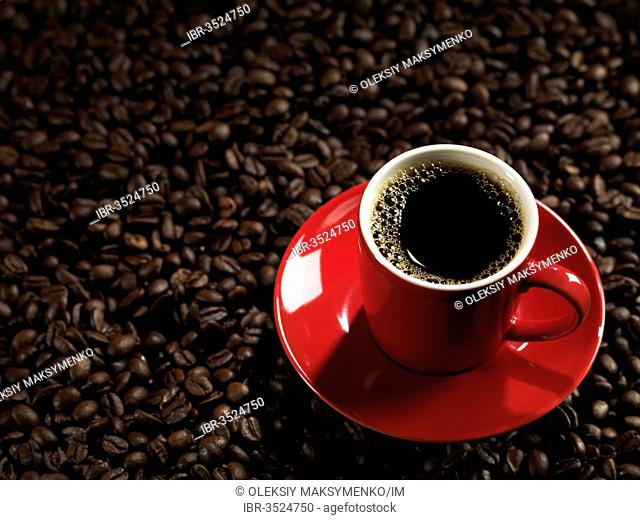 Red espresso cup on coffee beans