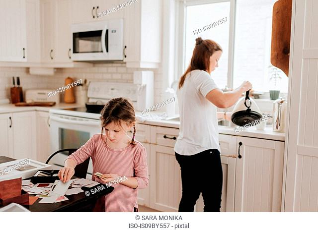Girl arranging cards in kitchen, mother pouring hot water in background