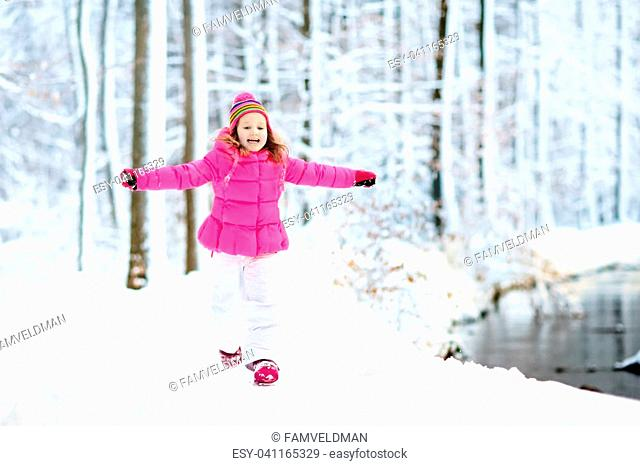 Child playing with snow in winter. Little girl in colorful jacket and knitted hat catching snowflakes in winter park on Christmas