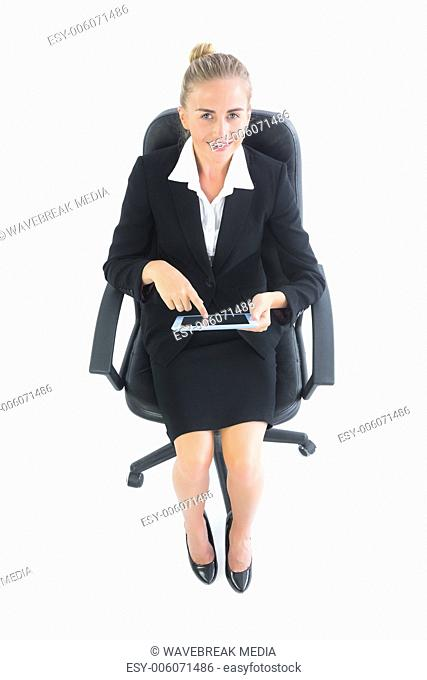 Laughing young businesswoman sitting on an office chair