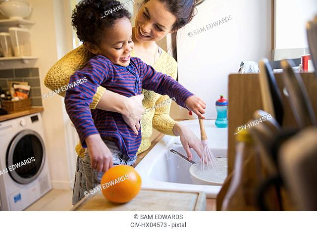 Happy mother and toddler son doing dishes at kitchen sink